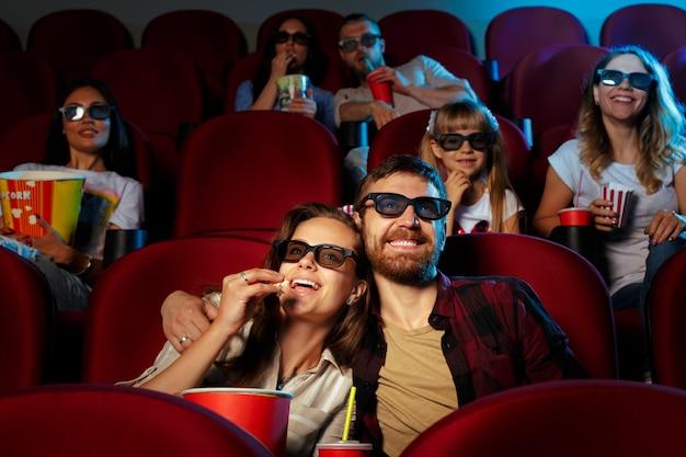 Amigos sentados en el cine ven la película comiendo palomitas de maíz y agua potable.