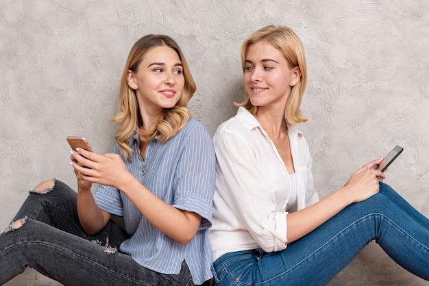 Amigos sentados espalda con espalda y mirándose