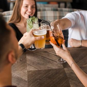 Amigos sentados juntos en el bar brindando un conjunto de bebidas