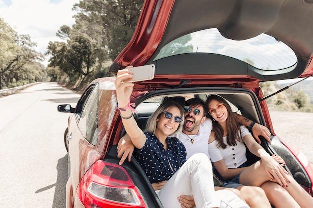 Amigos sentados juntos en el baúl del auto tomando selfie a través del teléfono móvil