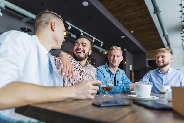 Amigos sentados juntos en el restaurante disfrutando de la bebida