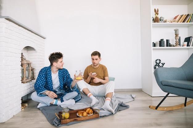 Amigos sentados en el piso comiendo comida deliciosa en casa