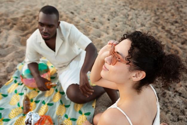 Amigos sentados en la playa de cerca