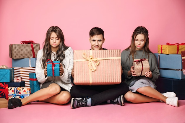 Amigos sentados entre regalos de navidad. chico con caja grande, mujer pequeña.