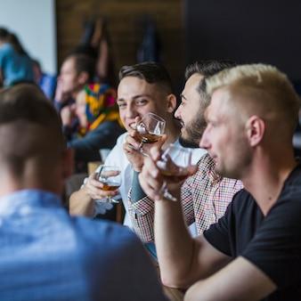Amigos sentados en el restaurante disfrutando de las bebidas
