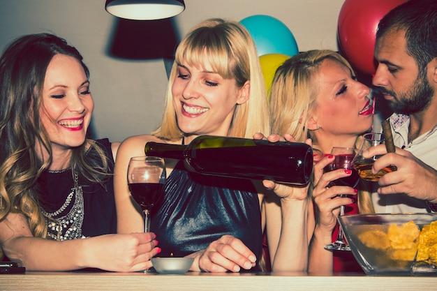Amigos sirviendo y bebiendo vino