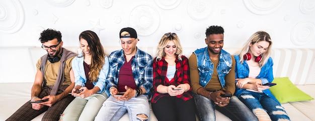 Amigos con smartphone en sofá en lugar interior