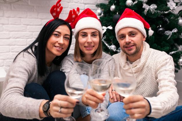 Amigos con sombreros de santa sentados cerca del árbol de navidad bebiendo vino