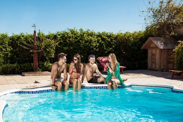 Amigos sonriendo, bebiendo cócteles, relajándose, sentados cerca de la piscina