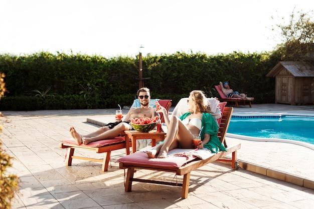 Amigos sonriendo, bebiendo cócteles, tumbados en tumbonas cerca de la piscina