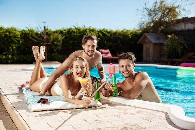 Amigos sonriendo, haciendo selfie, bebiendo cócteles, relajándose cerca de la piscina