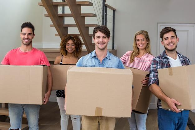 Amigos sonriendo mientras cargaban cajas de cartón