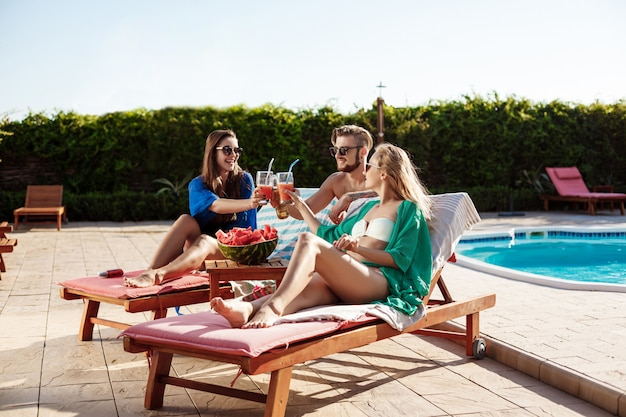 Amigos sonriendo, tomando el sol, bebiendo cócteles, tumbado cerca de la piscina