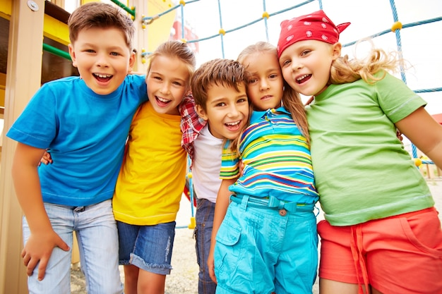 Amigos sonrientes abrazándose en el parque infantil