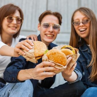 Amigos sonrientes al aire libre disfrutando de hamburguesas