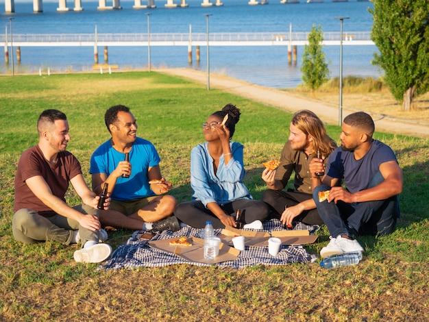 Amigos sonrientes alegres que tienen comida campestre en parque. jóvenes sentados en la hierba verde y comiendo pizza. concepto de picnic