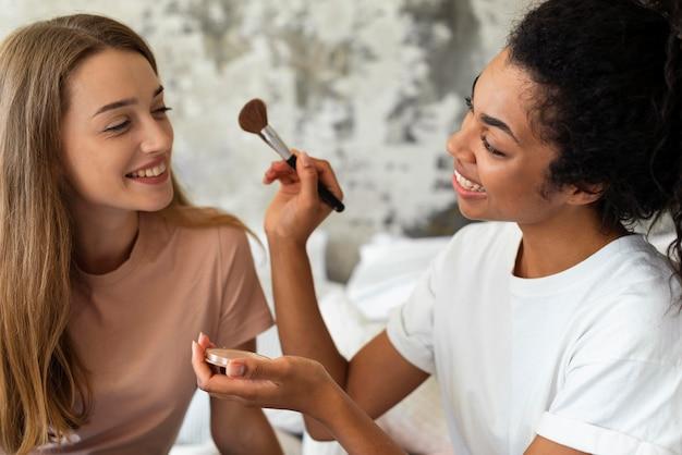 Amigos sonrientes ayudándose unos a otros con maquillaje
