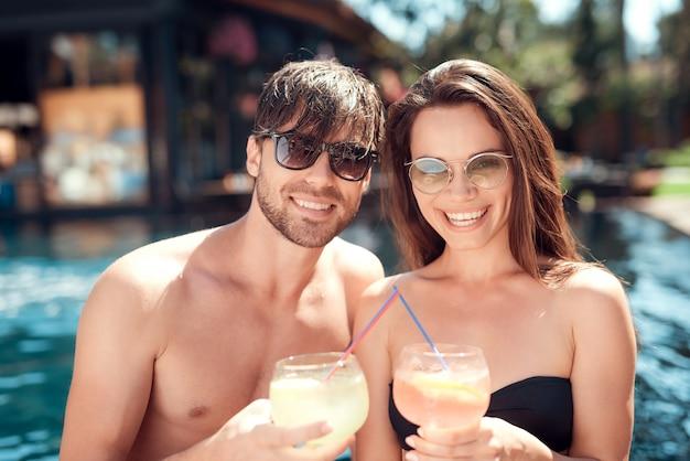 Amigos sonrientes bebiendo cócteles en la piscina