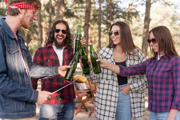 Amigos sonrientes brindando con cerveza sobre barbacoa