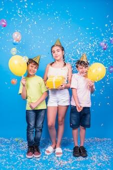 Amigos sonrientes celebran la fiesta de cumpleaños con un regalo; globos y confeti sobre fondo azul