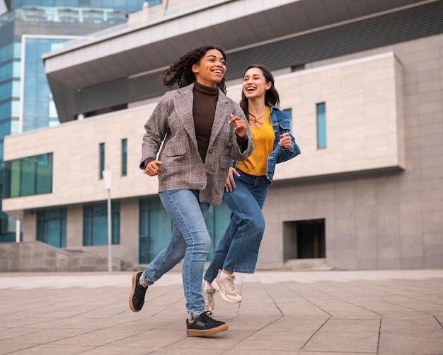 Amigos sonrientes corriendo juntos al aire libre