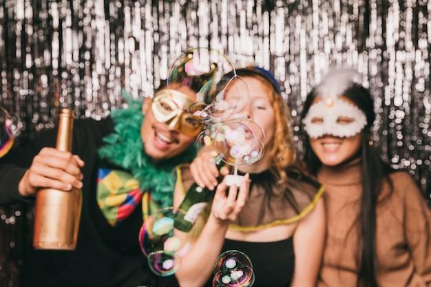 Amigos sonrientes divirtiéndose en la fiesta de carnaval