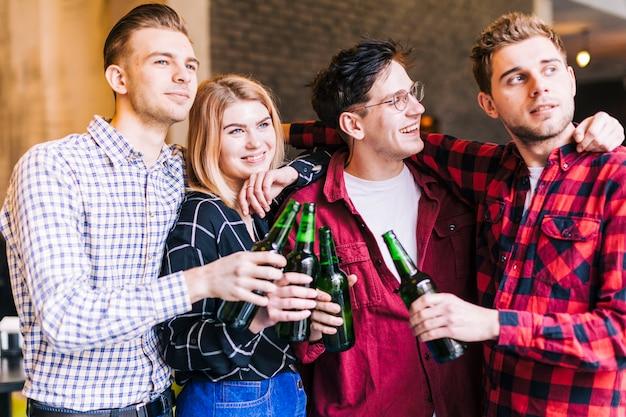 Amigos sonrientes felices que sostienen las botellas de cerveza verdes disponibles