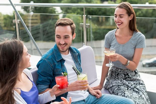Amigos sonrientes en una fiesta en la terraza