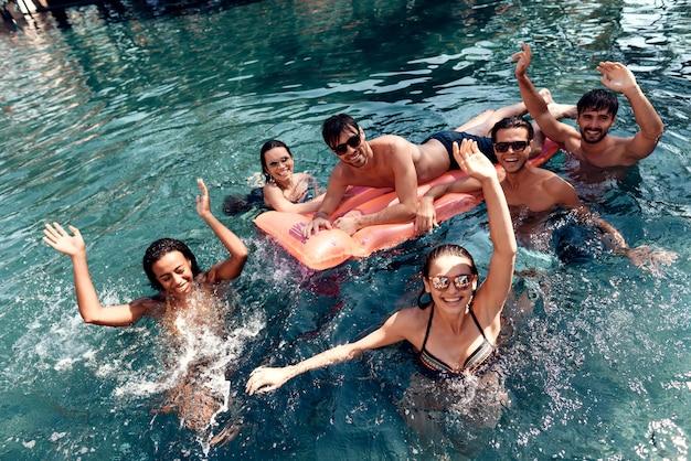 Amigos sonrientes jovenes que llevan las gafas de sol que ríen