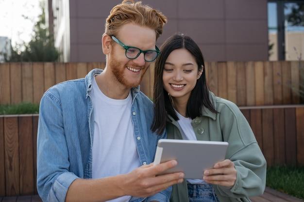Amigos sonrientes con mesa digital viendo videos de compras en línea