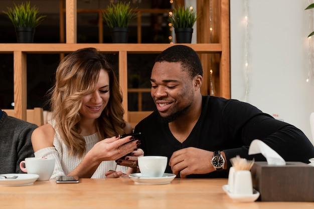 Amigos sonrientes mirando en el móvil
