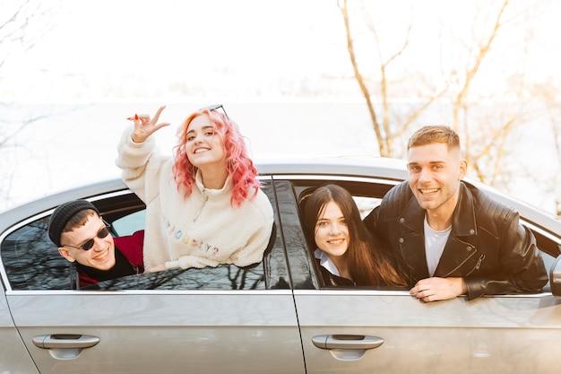 Amigos sonrientes mirando por la ventana del coche