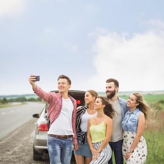 Amigos sonrientes que se colocan cerca del coche estacionado que toma el autorretrato