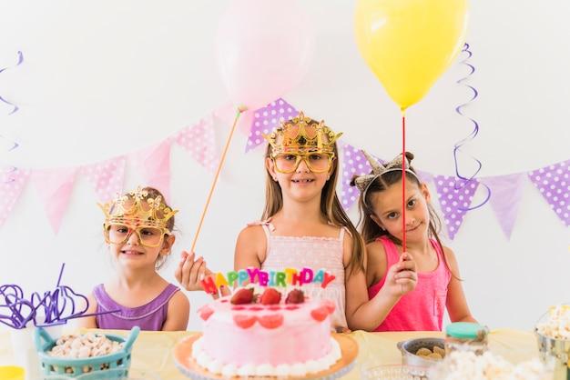 Amigos sonrientes que llevan la máscara de ojo que sostiene los globos que gozan en fiesta de cumpleaños