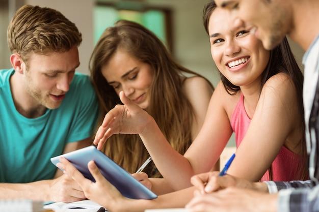 Amigos sonrientes que se sientan usando la pc de la tableta para el trabajo en equipo