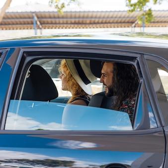 Amigos sonrientes que se sientan en coche en la gasolinera