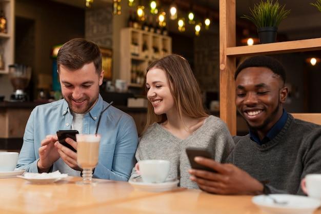 Amigos sonrientes que usan teléfonos en el restaurante
