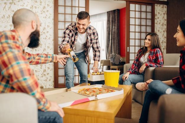 Amigos sonrientes que van a tomar una cerveza con pizza en la fiesta en casa. buena amistad, grupo de personas ocios juntos.