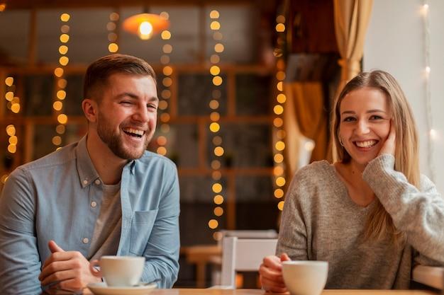Amigos sonrientes en el restaurante tomando café