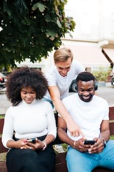 Amigos sonrientes sentados en el banco y usando el móvil