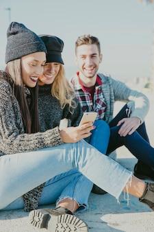 Amigos sonrientes sentados fuera