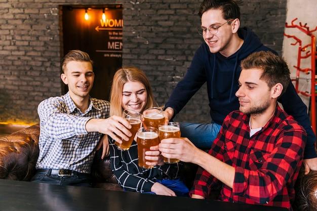 Amigos sonrientes sentados juntos tostando los vasos de cerveza