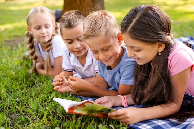 Amigos sonrientes sentados en una manta y leyendo