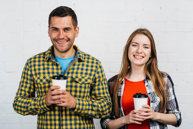 Amigos sonrientes sosteniendo su taza de café