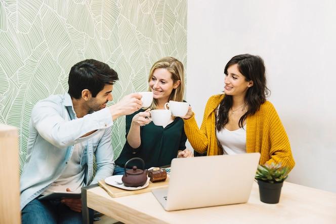 Amigos sonrientes tintineantes tazas de té