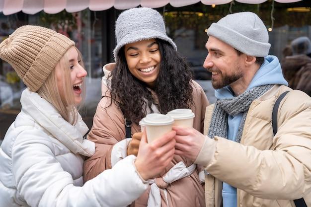 Amigos sonrientes de tiro medio con café
