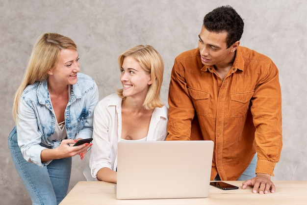 Amigos sonrientes usando una computadora portátil