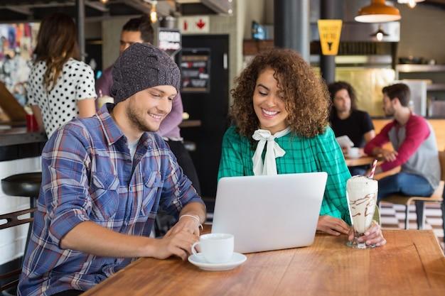 Amigos sonrientes usando laptop en restaurante
