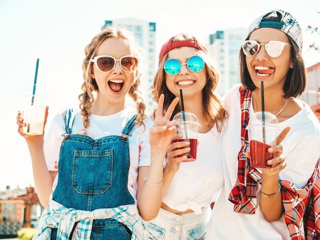 Amigos sosteniendo y bebiendo cóctel fresco licuado beber en vaso de plástico con paja