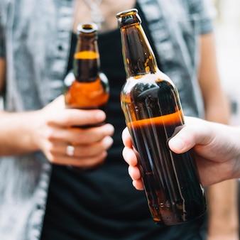 Amigos sosteniendo una botella de cerveza